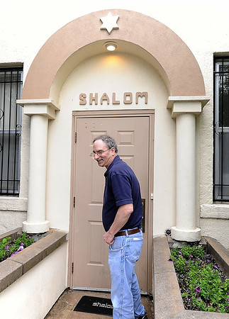 Paul Teverow, board member for the United Hebrew Congregation Temple at 702 S. Sergeant St., enters a door with a traditional Jewish greeting. The temple turned 100 years old this year.<br /> Globe | | Laurie Sisk