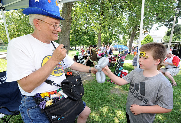 """""""Crazy Dave"""" Backus creates a balloon puppy for eight-year-old Trenton Lynch, of Webb City on Friday at the Friday Food Truck event in Carthage.<br /> Globe 