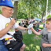 """Crazy Dave"" Backus creates a balloon puppy for eight-year-old Trenton Lynch, of Webb City on Friday at the Friday Food Truck event in Carthage.<br /> Globe 