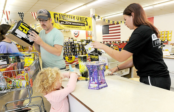 Johnnie Schofield, left, checks out with Black Market Fireworks employee Alyssa Lightfoot, 16, as four-year-old Velvet Schofield supervises the transaction on Wednesday at Black Market Fireworks on North Main Street.<br /> Globe | Laurie Sisk