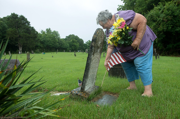 Globe/Roger Nomer<br /> Helen Hunter places a flag at the grave of Revolutionary War soldier Moses Duncan at the Cave Springs Cemetery on Thursday morning.