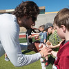 Globe/Roger Nomer<br /> Brayden Scott, a quarterback at Missouri Southern, helps Josh Anderson, 8, Joplin, with his football grip on Monday during the MSSU 2016 Cub Camp at Fred G. Hughes Stadium.