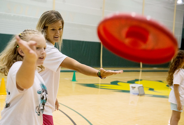 Globe/Roger Nomer<br /> Dru Clark, a Missouri Southern junior from Collinsville, Okla., helps Olivia Honey, 11, with her form during Thursday's Lifetime Sports Academy at the Leggett and Platt Athletic Center.