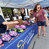 Logan Jolly, left, distributes a free bicycle helmet to Kaitlyn Merrick and her son Benjamin Merrick, 2 during Third Thursday in downtown Joplin through a program sponsored by Aaron Sachs & Associates. About 40,000 helmets have been given out since the program began two decades ago.<br /> Globe | Laurie Sisk
