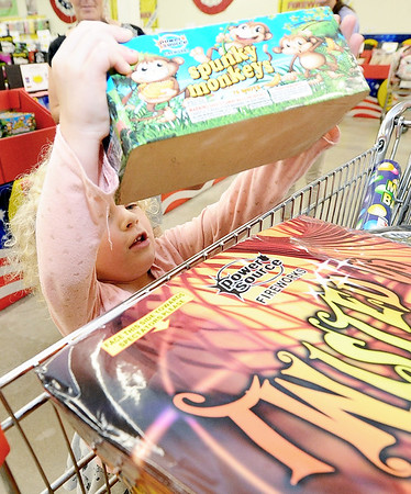 Four-year-old Velvet Schofield, of Granby, loads a selection into the family cart while shopping for fireworks on Wednesday at Black Market Fireworks on North Main street.<br /> Globe | Laurie Sisk
