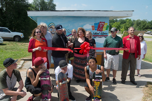 "Globe/Roger Nomer<br /> Chayann ""Silver"" Perez and Linda Teeter help cut the ribbon for the new murals at Ewert Skate Park on Wednesday."