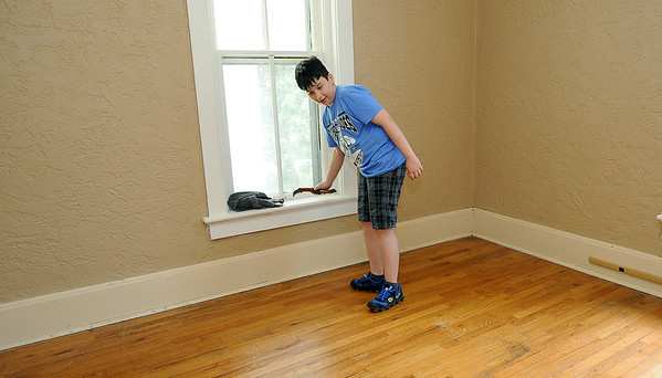 Grayson Willis, 12, delights at one of the artifacts he found ( an old bowie knife) in his new home at 1731 Annie Baxter. The home, built in 1887, was later occupied by Gabby Street.<br /> Globe | Laurie Sisk
