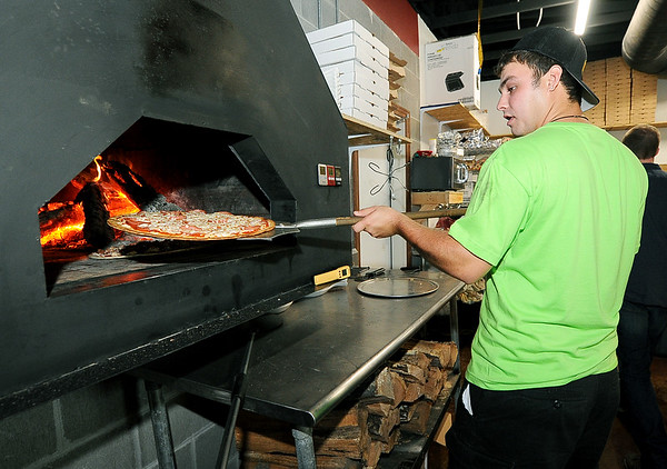Austin Baugh pulls a frshly-fired pizza from the wood-fired oven during a busy lunch at the 10th Street Cave Gang Pizza and Pub in Carthage on Thursday.<br /> Globe | Laurie Sisk