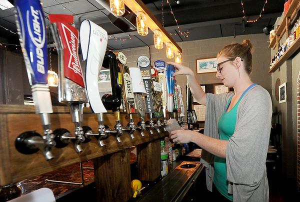 Katie Schwab pours a cold beer for a customer during a busy lunch at the 10th Street Cave Gang Pizza and Pub in Carthage on Thursday.<br /> Globe | Laurie Sisk