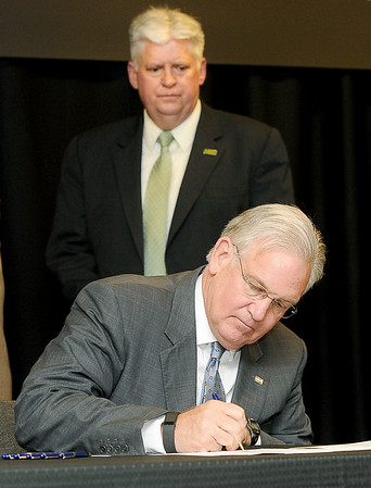 Missouri Gov. Jay Nixon, flanked by Missouri Southern President Alan Marble, signs a bill to add $262 million for improvement projects to the state's universities, including $16 million to MSSU on Thursday at MSSU.<br /> Globe | Laurie Sisk
