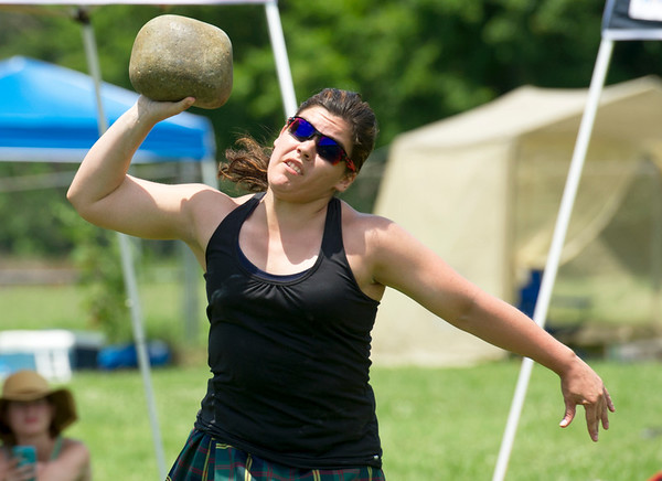 U.S. Marine Corps 1st Lt. Cheyann Essley, of Quantico, Va., launches a large boulder during the bramar stone competition on Saturday during the Scottish Highland Games at the Field of Dreams. Essley is originally from Cassville.<br /> Globe | Laurie Sisk
