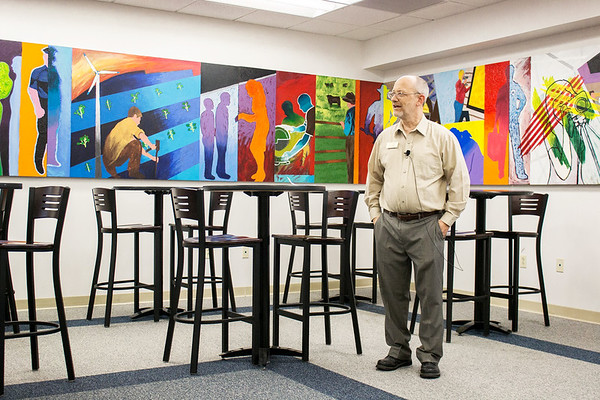 "Photo Courtesy of Crowder College<br /> Allen Bishop, a recently retired art instructor at Crowder College, talks about the mural titled ""Plan, Lean, Care, Create, Serve,"" created by students in the Arnold Farber Building on Wednesday."