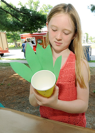 Eight-year-old Paisley Woodall creates a pineapple cup at the Carthage Art Feeds booth on Friday at the Friday Food Truck event in Carthage.<br /> Globe | Laurie Sisk