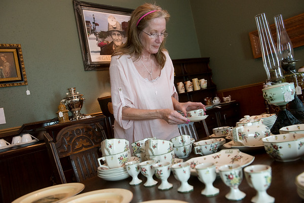 Globe/Roger Nomer<br /> Vicky Horbury arranges a tea set at Bordello Antiques on Wednesday.