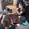 Marife Ponce serves a fresh wood-fired pizza to customers during a busy lunch at the 10th Street Cave Gang Pizza and Pub in Carthage on Thursday. Pictured clockwise from the lower left: Robin Paul, Eden Paul, Karly Paul and Lydia Youngworth.<br /> Globe | Laurie Sisk