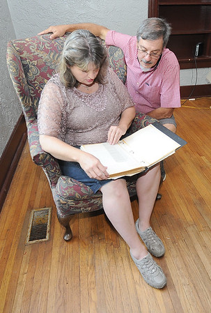Michelle and Jerry Willis look through a scrapbook left in their new home, which chronicles the house's rich history. The book has been left in the house and passed from owner to owner.<br /> Globe | Laurie Sisk