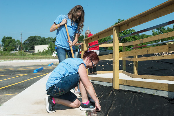 Globe/Roger Nomer<br /> April Arnall, bottom, and Jessie McNally, with Women of AT&T, help with landscaping at Crosslines on Friday as part of the United Way's Day of Action.