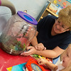 Globe/Roger Nomer<br /> Rebecca Spencer shows a student a frog at the Missouri Southern Early Childhood Development Center on Friday.