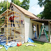 HistoriCorps volunteers work to preserve the exterior of George Washington Carver's first schoolhouse on Young street in Neosho on Wednesday.<br /> Globe   Laurie Sisk