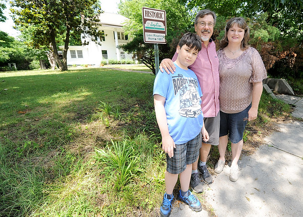 The Willis family stands in front of their new home at 1731 Annie BAxter St. on Friday. The home, originally built in 1887 by John Riesling, also was inhabited by Gabby Street, former St. Louis Cardinals player and famed sports broadcaster. From the left: Grayson Willis, 12 and his father, Jerry Willis and mother Michelle Willis.<br /> Globe | Laurie Sisk