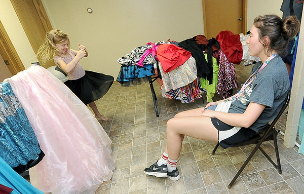 "Camper Leigha Y. delights in the dress she picked out in the ""Say Yes to the Dress Boutique"" as her companion Keri Walter looks on Thursday at Camp Quality near Neosho. Girls get to chose from a wide variety of dresses for the annual dance - the last of a week full of activities for kids battling cancer.<br /> Globe 