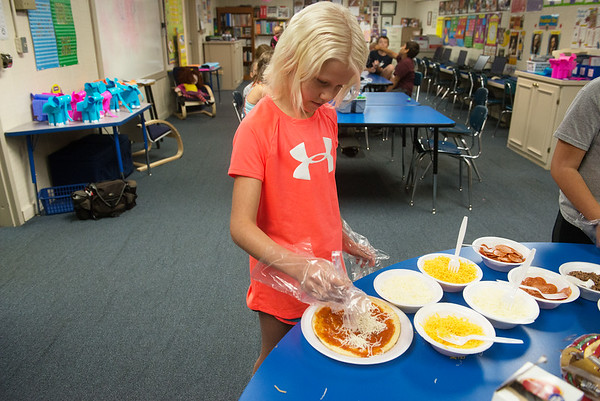 Globe/Roger Nomer<br /> Paycie Clifford, fifth grade, makes a pizza as part of an exercise on fractions at Galena on Wednesday.
