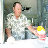 Allen Stinebock, of Sno Biz, serves an orange shaved ice to a customer on Friday at the Friday Food Truck event in Carthage.<br /> Globe | Laurie Sisk