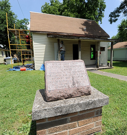 HistoriCorps volunteers work to preserve the exterior of George Washington Carver's first schoolhouse on Young street in Neosho on Wednesday.<br /> Globe | Laurie Sisk