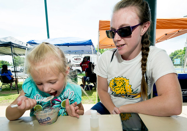 Four-year-old Annabelle Lucas digs into some ice cream as her mother, Brooke Praytor looks on during the East Town Ice Cream Social on Saturday at Ewert Park.<br /> Globe | Laurie Sisk