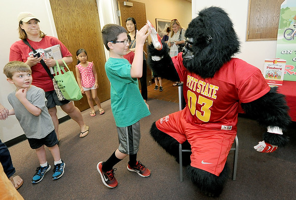 Nine-year-old Kannon Brasch gets a high five from Gus the Gorilla during Macot Day at the Joplin Public Library. Seven mascots from area sports teams and local businesses were on hand to greet children during the event. Globe | Laurie Sisk