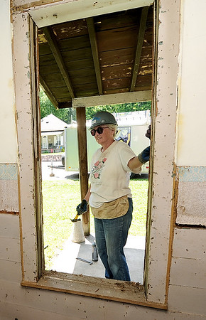 HistoriCorps volunteer Cheryl Hiipakka, of Chicago, works to remove old window trim on George Washington Carver's first schoolhouse on Young street in Neosho on Wednesday.<br /> Globe | Laurie Sisk