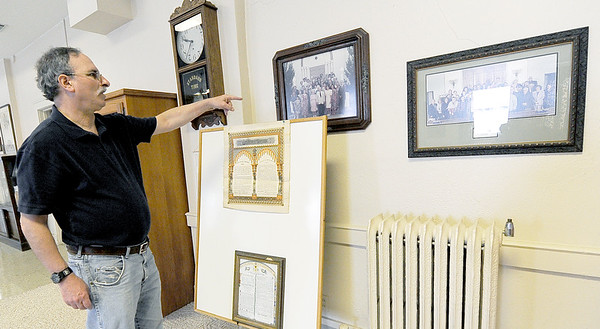Paul Teverow, board member for the United Hebrew Congregation Temple at 702 S. Seargeant St., points to photographs of congregations throughout various annivesaries. The temple turned 100 years old this year.<br /> Globe | | Laurie Sisk