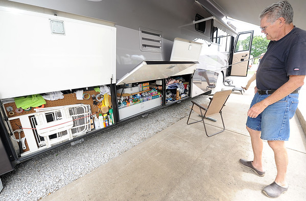 Full-time RVer Allen Anglin looks through the cargo holds of his RV , which contain tools, househol items and extra food. <br /> Globe | Laurie Sisk