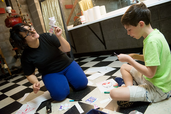 Globe/Roger Nomer<br /> Christy Hernandez helps Phillip Motazedi, 11, with making finger puppets at the Joplin Little Theatre's summer camp Puppet Plays on Monday. The camp runs through the end of the week.