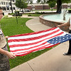 From the left: Boy Scout Troop 103 scouts Riley Bowers, 14 and Michael Bowman, 15, stretch a large U.S. flag out as they demonstrate the proper protocol for folding an American flag on Tuesday afternoon at Spiva Park.<br /> Globe | Laurie Sisk