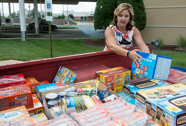Globe/Roger Nomer<br /> Amy Howe, marketing manager for Arvest Bank, loads food donations on Tuesday at the bank.