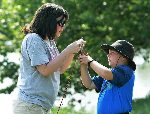 From the left: Sherry Noller, of Webb City, helps her nine-year-old son, Derak Noller, tie off his line  during Kid's Fishing Day on Saturday at Kellogg Lake in Carthage. The event featured information booths, activities, food and fishing - all free of charge to guests.<br /> Globe | Laurie Sisk