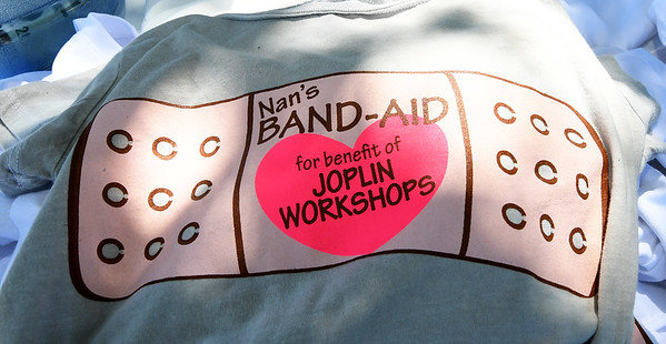 T-shirts sold to benefit former workers of the Joplin Workshops laundry, which burned in March, lay on a table during a benefit concert named Nan's Band-Aid. Proceeds of the event will go to help the 40 employees who lost their jobs after the fire. The event was named after the late Nancy Clarkson, longtime employee at the workshop.<br /> Globe | Laurie Sisk