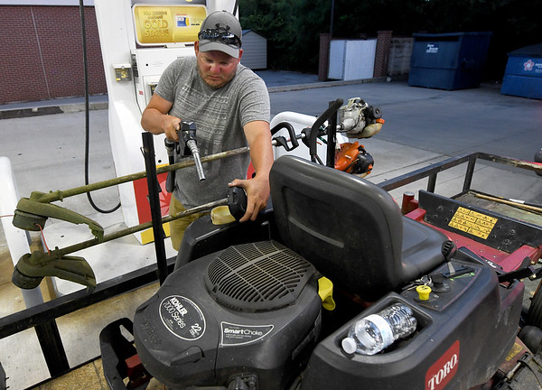 "Jeremiah Bitticks, of Jay's Property Management, gasses up his van and mower on Wednesday night at Doc's Stop on Maiden Lane. In addition to saving fuel by gassing up at night, Bitticks said ""It's just one less thing to do in the morning before I go to work.""<br /> Globe 