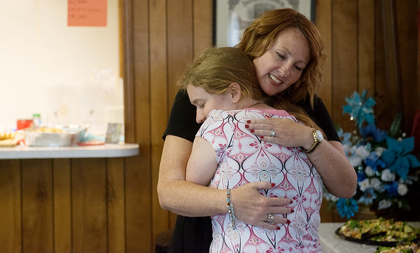 Globe/Roger Nomer<br /> Candace Gayoso, Galena city attorney, gives a hug to Mali House on Friday during the luncheon in Galena at St. Patrick's Hall.