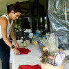 Boys and Girls Club of Southwest Missouri Unit Director Sarah McMullen arranges raffle items on a table for the Clubbing for the Club charity golf tournament on Thursday at Twin Hills Golf and Country Club. The tournament features about 100 golfers and is a largest fundraiser of the year for the club.<br /> Globe | Laurie Sisk