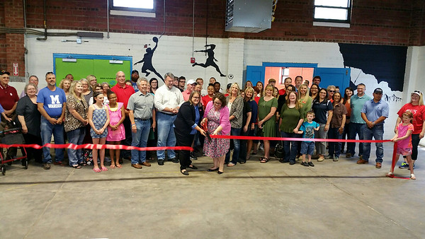 Executive director of the Boys & Girls Club of Ottawa County Mackenzie Garst, left, cuts the ribbon during the grand opening of the Armory building, the club's new home. The children will now be located in Riverview Park next to playgrounds, baseball fields and the municipal pool.   Kimberly Barker/Joplin Globe