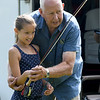 Steve Werries, of Mako Fly Fishers, teaches Taneshia Abbasi, 10, the correct technique for fly fishing during Kid's Fishing Day on Saturday at Kellogg Lake in Carthage. The event featured information booths, activities, food and fishing - all free of charge to guests.<br /> Globe | Laurie Sisk