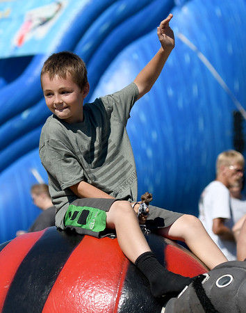 Keyton Brady, 10, of Neosho, smiles as he takes a spin on one of about a dozen carnival rides on Saturday during the Celebrate Neosho Air Show at Neosho's Hugh Robinson Airport. The day-long event featured carnival rides, vendors, helicopter rides, tandem sky diving and more. The excitement was capped off by a large airshow and fireworks display. As many as 5,000 spectators were expected to attend the fourth annual event.<br /> Globe | Laurie Sisk