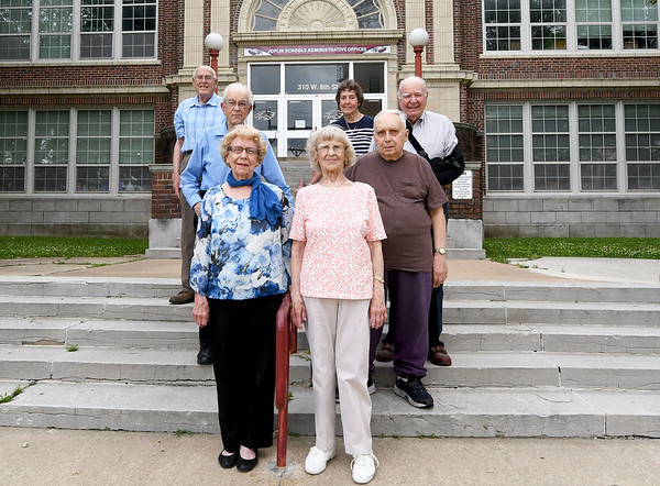 Front row to back row, from the left: Class of 1947 members Cecelia Wiggins Fisher, Wilma Wiedeman McNab, Charles Miller, Milo Harris, Keith Adams, Henry Robertson and Phyliss White Detar pose for a photo on Saturday outside their Alma Mater, The old Joplin High School. The group is organizing their class' 70th reunion.<br /> Globe | Laurie Sisk