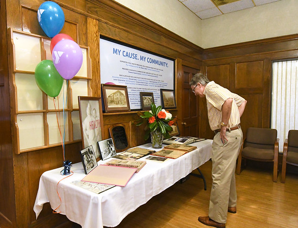 David Austin looks at historic photographs of the Downtown YMCA on Wednesday afternoon at a reception ahead of the closing of the location.<br /> Globe | Laurie Sisk