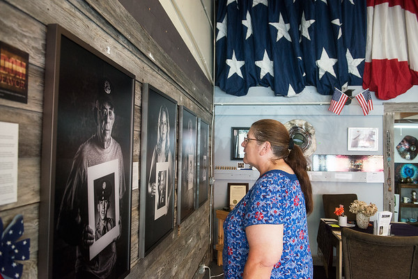 """Globe/Roger Nomer<br /> Denise Ryburn, Clairemore, looks at Steve Snyder's photos in the """"Freedom Endeavor"""" exhibit at the Urban Art Gallery on Monday."""