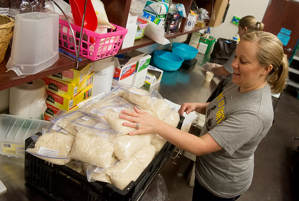 Globe/Roger Nomer<br /> Jana Smith, branch administrator with Arvest Bank, sorts rice on Friday at Crosslines as part of the United Way's Day of Caring.