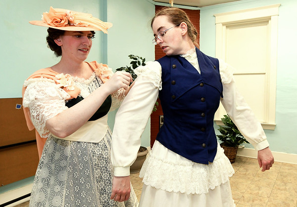 From the left: Emily Ellis, dressed in 1916 attire, assists sister Kay Ellis with her 1909 ensemble.<br /> Globe | Laurie Sisk