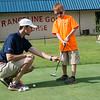 Globe/Roger Nomer<br /> Daryn Buhollt, golf pro at Schifferdecker Golf Course, helps Trenton Loyd, 10, Joplin, with his swing on Monday during the Joplin Golf Foundation's Joplin Junior Golf Tee It Up Program at Rangeline Golf Course. The free program was open to students in third through eighth grade and has been running in the summer since 1970.